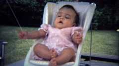 1971: Baby flailing legs and arms around in small white chair. Stock Footage
