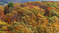 Low flight along wooded ridge in fall colors Stock Footage