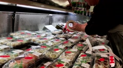 Worker putting discount price on sushi bar inside T&T supermarket Stock Footage