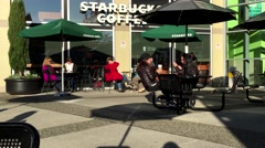 One side of people drinking Starbucks coffee on sunny day Stock Footage