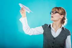 Stock Photo of Fly fear. Woman holding airplane in hand.