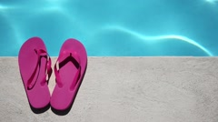 Pink slippers near swimming pool Stock Footage