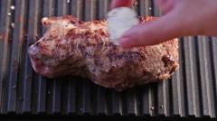 Grilling steak with a piece of melting butter Stock Footage