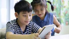 Little asian boy and girl take a photo with tablet computer Stock Footage