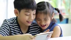 Little asian boy with tablet computer and little girl playing together - stock footage
