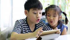 Little asian boy with tablet computer and little girl playing together Stock Footage
