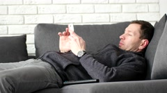 Attractive man lies on couch watching TV and holding remote - stock footage