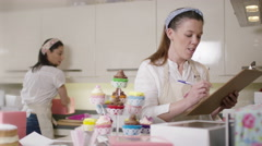 4K Female business partners in home bakery business packing cakes in boxes Stock Footage