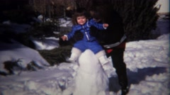 1974: Young girl blue coat winter snowman mother plays. Stock Footage