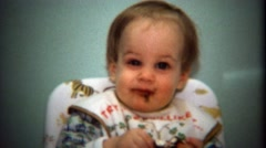 1974: Baby getting messy eating big chocolate candy treat. - stock footage