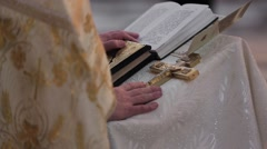 Oath at the newlyweds on luxuriously decorated bible. Hands of men  in the - stock footage