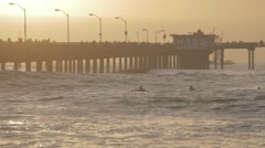 Surfers paddle out at golden hour - stock footage