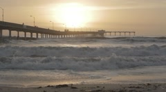 Distant surfers watching waves at golden hour - stock footage