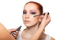 Professional Make-up artist doing glamour with red hair model makeup.  Isolated - stock photo