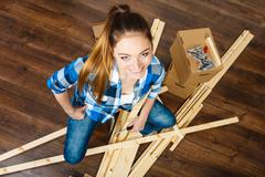 Stock Photo of Woman moving into apartment assembly furniture.