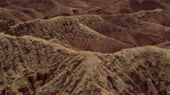 Low, fast flight over eroded hillsides - stock footage