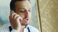 Attractive man in white shirt and suspenders on the phone Stock Footage