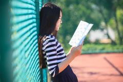 asian girl and school book in hand toothy smiling face with happiness emotion - stock photo