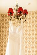 Beautiful  wedding dress hanging on a lamp in the room. Bridal morning - stock photo