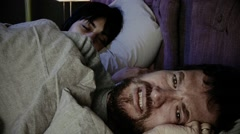 Sad man crying in bed while girlfriend is sleeping at night Stock Footage