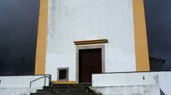 Tilt up to old small yellow white chapel church, dark cloudy sky, Portugal Stock Footage