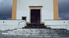 Scary spooky small yellow white chapel church, tilt up, Portugal - stock footage