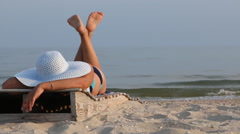 Woman lying in a lounger on the beach Stock Footage