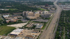 Flight along freeway past Memorial Hermann Hospital complex in Houston. Shot in Stock Footage