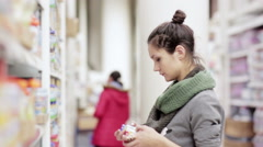 Young woman chooses baby food in the supermarket Stock Footage