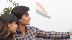 Couple taking selfie stick mobile camera with Indian national flag in background Stock Footage