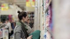 Young woman chooses towels in the supermarket Stock Footage