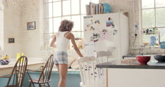 Happy curly haired  girl dancing wearing pyjamas at home in kitchen - stock footage