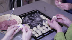 People mold dumplings and put on a baking sheet Stock Footage