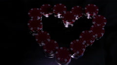 Illuminating stacks with casino chips like a heart on black background - stock footage