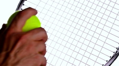 Hand putting set of two new tennis balls over tennis racket on white background - stock footage