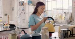 Pretty hispanic girl making hot drink wearing pyjamas at home Stock Footage