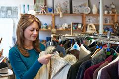 Female Shopper In Thrift Store Looking At Clothes - stock photo