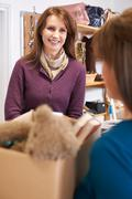 Woman Donating Unwanted Items To Charity Shop - stock photo