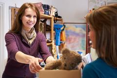 Woman Donating Unwanted Items To Charity Shop Stock Photos