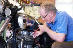 Senior Man Working On Vintage Motorcycle In Garage - stock photo