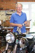 Senior Man Restoring Vintage Motorcycle In Garage - stock photo