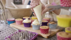 4K Woman with home bakery business piping cream onto cupcakes - stock footage