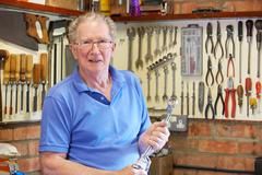 Senior Man in Workshop Standing With Tools Stock Photos
