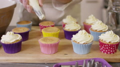 4K Woman with home bakery business piping cream onto cupcakes Stock Footage