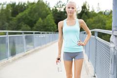 Stock Photo of Smiling female runner taking a break after running