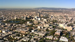 Flight approaching Los Angeles high-rises with valley and smog beyond. Shot in - stock footage