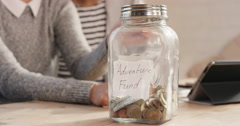 Happy mixed race couple saving money in adventure fund jar - stock footage