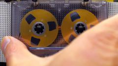 Hand inserts a cassette into the tape recorder and play music - stock footage