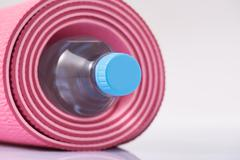Rolled up yoga mat with bottle of water inside - stock photo