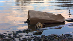 Litter floating near shore of river, close-up to wide view - stock footage